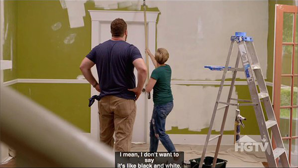 "A man and woman, painting a green room with white primer. At the bottom are closed captions on three lines that read: Line 1: ""I mean, I don't want to"" Line 2: ""say"" Line 3: ""It's like black and white"""