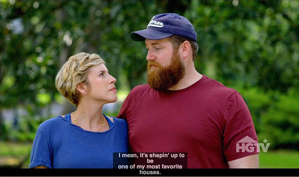 "A woman (left) and man(right), standing in front of a blurred green forest background. At the bottom are four captions that read, Line 1: ""I mean, it's shapin' up to"" Line 2: ""be"" Line 3: ""one of my most favorite"" Line 4: ""houses."""