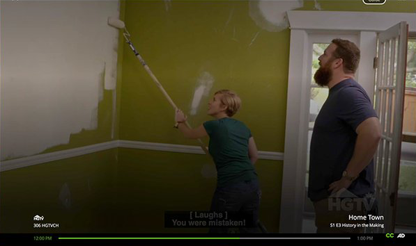 "A man and woman, in the corner of a green walled room, painting white primer on the walls. At the bottom are closed captions on two lines that read: Line 1: ""[Laughs]"" Line 2: ""You were mistaken!"""